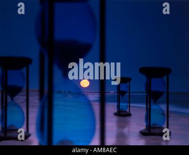 Moment Factory image conceptuelle de sabliers placés dans nuit paysage surréaliste Banque D'Images