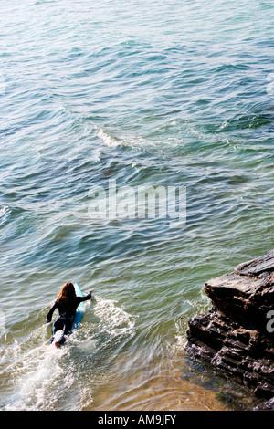 Femme couchée sur une planche de surf dans l'eau. Banque D'Images