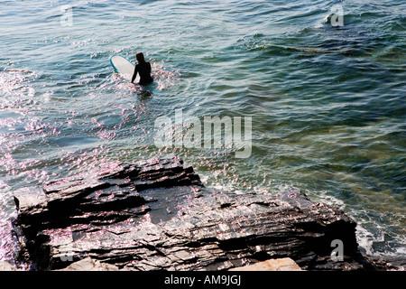 Femme assise sur une planche de surf dans l'eau. Banque D'Images