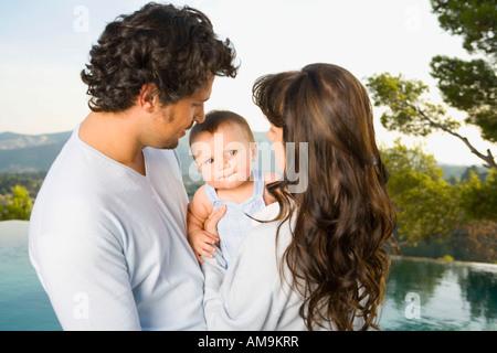 Couple tenant un bébé par une piscine à débordement à l'extérieur. Banque D'Images