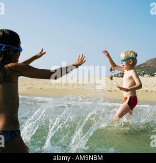 Jeune fille et un jeune garçon jouant sur la plage. Banque D'Images