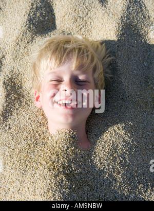 Jeune garçon enterré dans le sable en riant. Banque D'Images