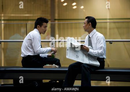 Deux hommes d'avoir une pause déjeuner sur un banc Banque D'Images