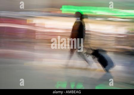 En passant par une image floue intentionnellement d'une femme se déplaçant rapidement si un aéroport tirant une Banque D'Images