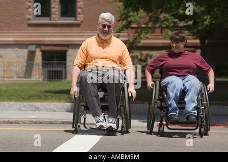 Homme d'âge moyen et une femme d'âge moyen traversant une route en fauteuil roulant Banque D'Images