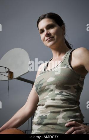 Woman holding basket-ball avec net en arrière-plan Banque D'Images