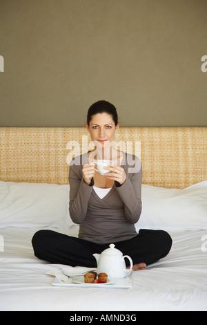 Femme prenant le thé on Bed