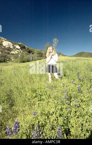 Modifié numériquement, à fort contraste de l'image fille blonde dans les champs remplis de fleurs au printemps lupin Banque D'Images