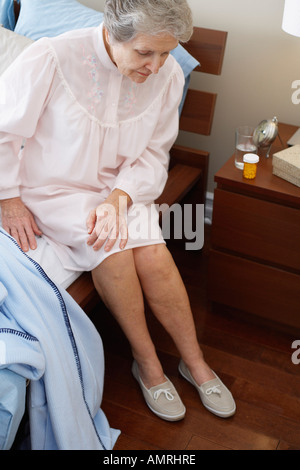 Personnes âgées Woman Sitting on Bed Banque D'Images
