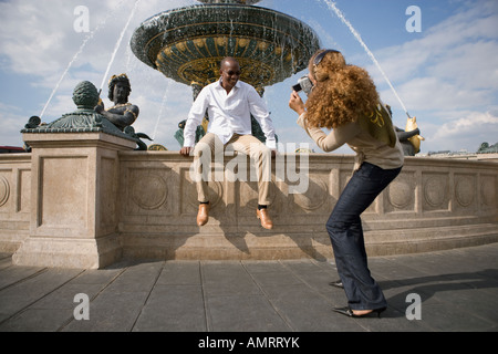 African woman taking photograph of boyfriend Banque D'Images