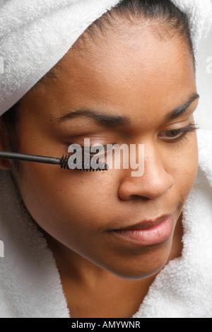 Femme en blanc peignoir et serviette blanche près de le miroir de maquillage Mascara MR-12-17/18-07 Banque D'Images