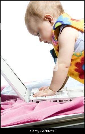 Profil d'un bébé avec un ordinateur portable Banque D'Images