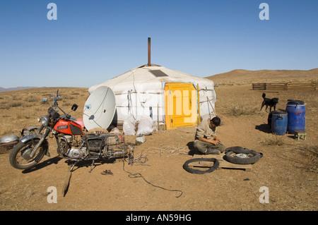 La Mongolie centrale zone Lun homme réparait sa moto en face de yourte Banque D'Images