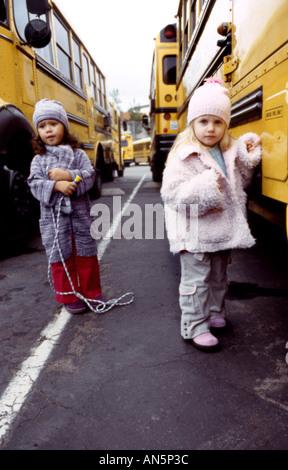 Deux jeune fille pose devant un autobus scolaire Banque D'Images