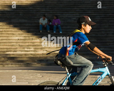 Mexique Guanajuato Young boy riding bicycle in plaza près de l'Alhondiga couple sitting on steps dans l'ombre Banque D'Images