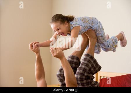 Jeune fille africaine en équilibre sur les pieds du père