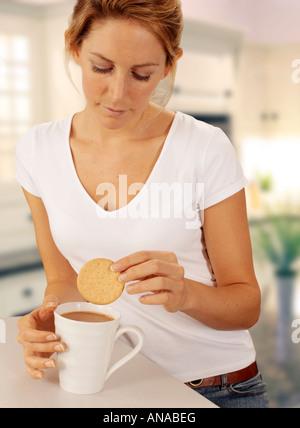 Femme en biscuit tremper cuisine dans la tasse de thé Banque D'Images