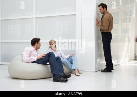 L'homme à l'écoute de conversation entre deux ragots business people in office Banque D'Images