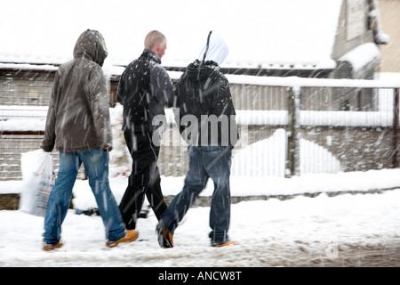 Trois jeunes hommes marchant le long sentier en pleine tempête Banque D'Images