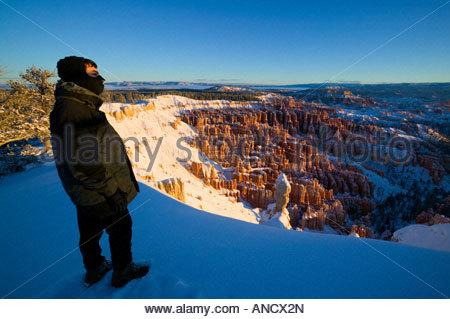 Un randonneur admire la vue de l'amphithéâtre de Bryce Canyon en Utah sur un froid matin d'hiver après les chutes de neige fraîche.