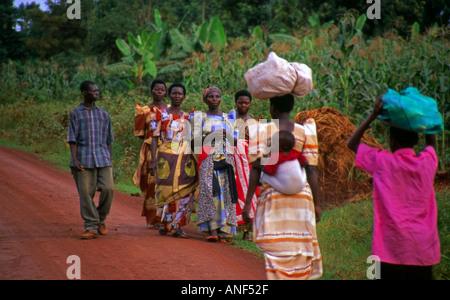 Les femmes autochtones dans des vêtements traditionnels colorés à pied porter enfant lots et des marchandises sur Banque D'Images