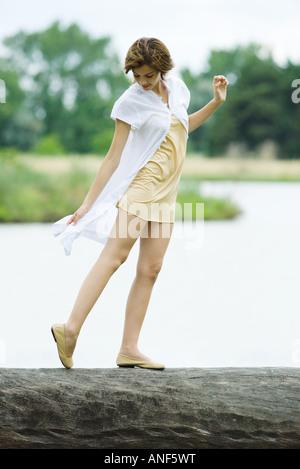Young woman walking along log en regardant le pied, pleine longueur Banque D'Images