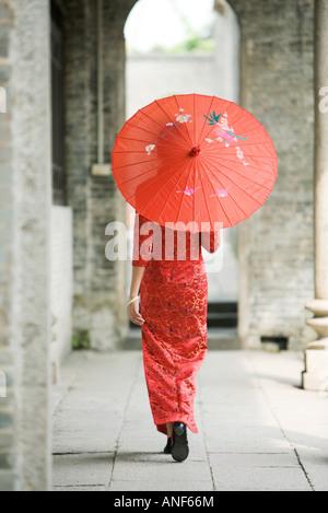 Jeune femme habillé en vêtements traditionnels chinois marcher avec parasol, vue arrière Banque D'Images