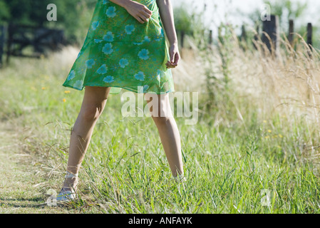 Young woman standing in rural field avec jambes écartées, cropped view Banque D'Images