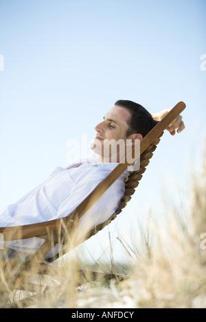 Jeune homme assis dans une chaise Banque D'Images