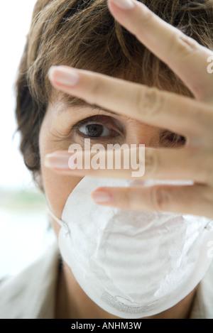 Femme portant un masque de la pollution, à l'intermédiaire de doigts à huis clos Banque D'Images