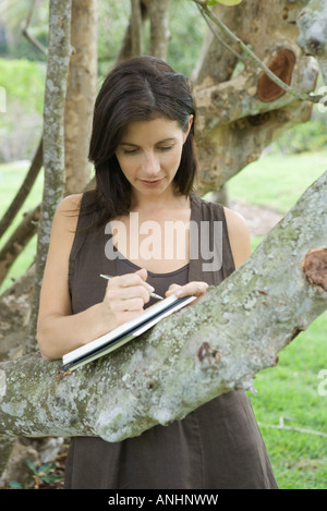 Woman leaning against tree branch, écrit dans un livre, regardant vers le bas Banque D'Images