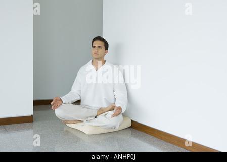 Homme assis en position du lotus le coussin, looking away Banque D'Images