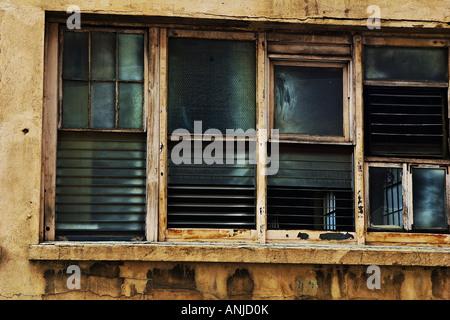 Quatre, à persiennes, cadre en bois en décomposition dans le vitrail et windows 12.2005 tan, mur en stuc sur le Banque D'Images