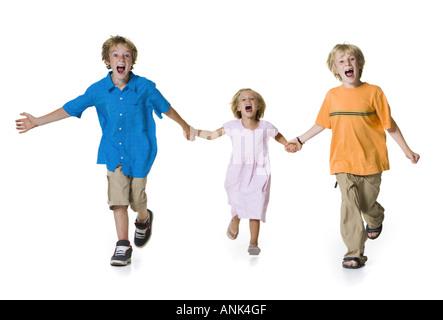Portrait de deux frères courir avec leur soeur. Banque D'Images