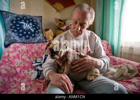 Un homme tient son petit chien qui a été brutalement coupé avec un couteau par jeunesse et reçu des centaines de Banque D'Images