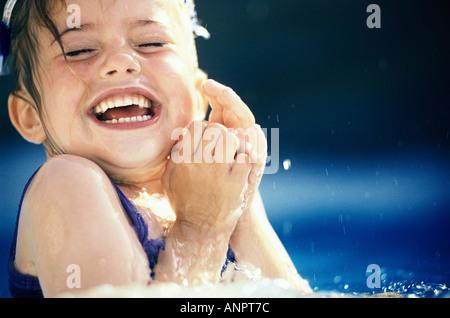 Portrait d'une fille d'être éclaboussé dans une piscine Banque D'Images