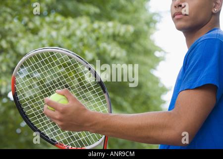 Mid section view of a Teenage boy holding une raquette de tennis et une balle de tennis