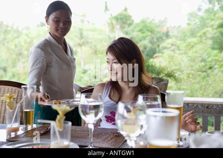 Jeune femme assise à table, table de compensation serveuse Banque D'Images