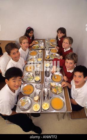 Des dîners de repas scolaires sains Groupe d'étudiants de l'école junior multiethnique ayant déjeuner sain et équilibré Banque D'Images