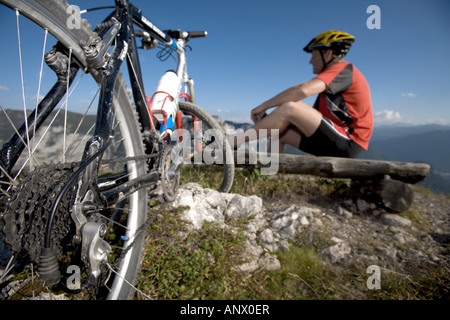 Mountainbiker ayant une pause sur un banc en bois, de l'Autriche, Styrie, Alpes Banque D'Images