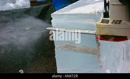Coupe de scie à chaîne un bloc de glace Banque D'Images