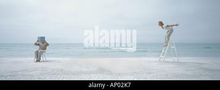 On beach, man holding up livre en face de visage tout en femme sur l'escabeau lui crie Banque D'Images