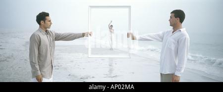Deux hommes tenant cadre, woman waving dans le cadre dans la distance, on beach Banque D'Images