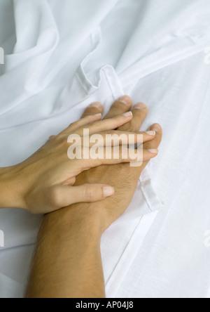 La main de femme sur le dessus de l'homme, sur des feuilles Banque D'Images