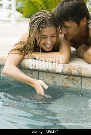 Jeune couple couché en bord de piscine, femme trempant dans l'eau à la main Banque D'Images