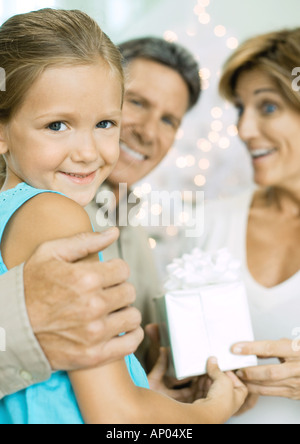 Petite fille donnant les grands-parents cadeau de Noël Banque D'Images