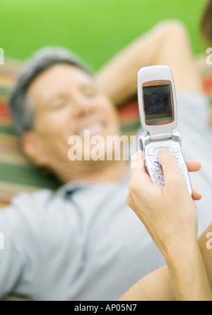 En tenant la main photo de l'homme dans l'hamac avec téléphone photo Banque D'Images
