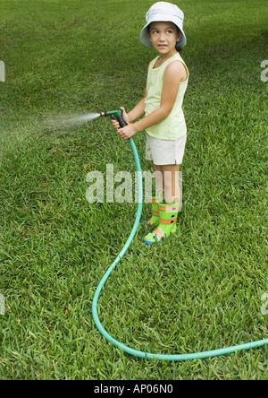 Petite fille debout avec tuyau de jardin Banque D'Images
