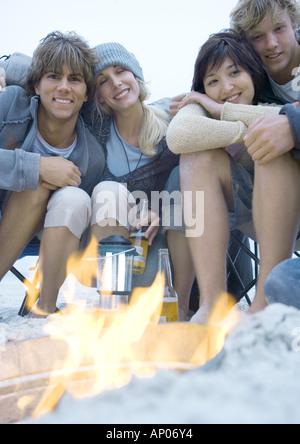 Les amis des jeunes adultes assis autour de feu de camp Banque D'Images