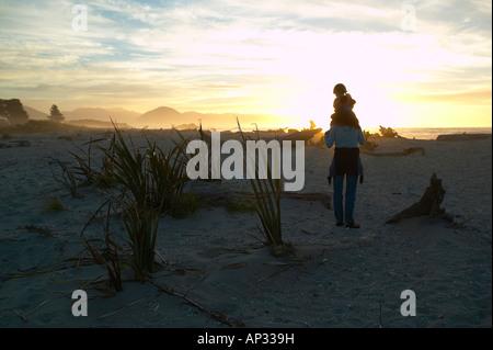 Randonnées dans les journaux entre plage, mère portant l'enfant, plage près de Haast, Westcoast, île du Sud, Nouvelle Banque D'Images